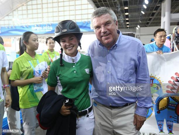 IOC President Thomas Bach poses with Macarena Chiriboga Granja of Ecuador as he watches Equestrian Jumping International Team Round 2 match at...
