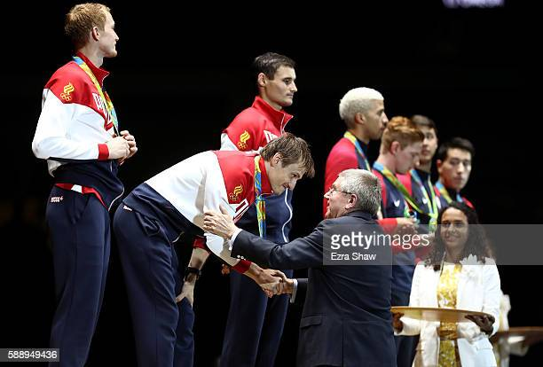 President Thomas Bach presents Alexey Cheremisinov of Russia with a gold medal during the podium celebration for the Men's Team Foil event on Day 7...
