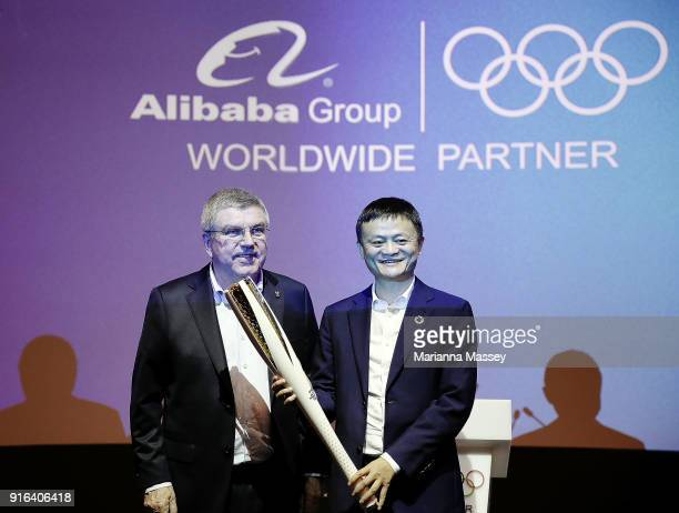 President Thomas Bach presents an Olympic Torch to Alibaba Group Executive Chairman Jack Ma during the unveiling of the Alibaba Showcase at the...