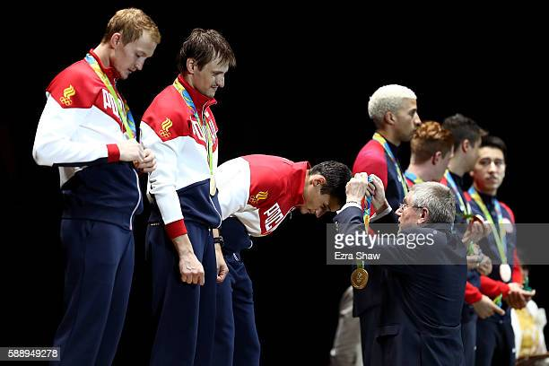 President Thomas Bach presents Artur Akhmatkhuzin of Russia with a gold medal during the podium celebration for the Men's Team Foil event on Day 7 of...