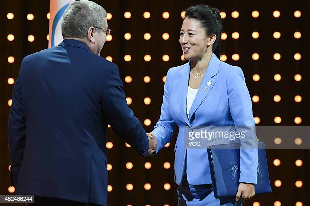 IOC president Thomas Bach shakes hands with Chinese twotime Olympic champion Yang Yang during the bid presentation to host the 2022 Winter Olympics...