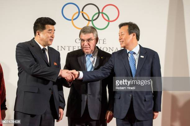 President Thomas Bach stands while Mr Kim Il Guk DPR Korea Sport Minister and President of the Olympic Committee and Mr Jong Whan Do South Korea...