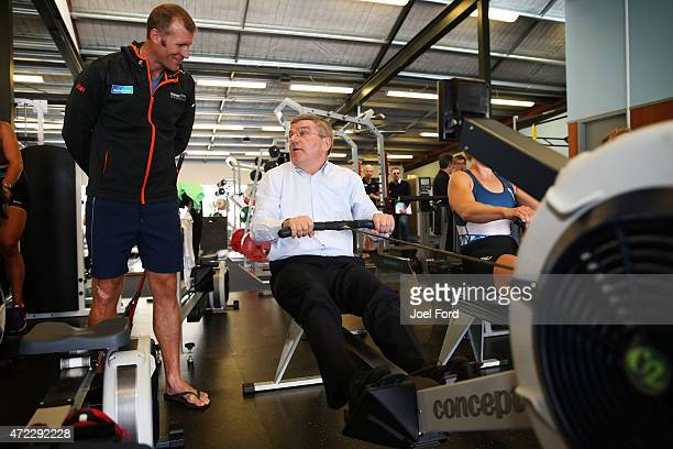 President Thomas Bach tries a rowing machine while New Zealand rower Mahe Drysdale watches on during a visit to the New Zealand Rowing High...