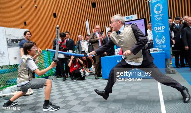 President Thomas Bach tries mock fencing with Japanese junior high school student Yui Hashimoto during an event marking one year before the start of...