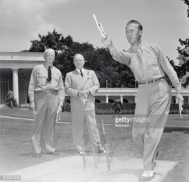 President Truman and Admiral Chester Nimitz get a few pointers in trick horseshoe pitching from Jimmy Risk world's champion trick and fancy horseshoe...