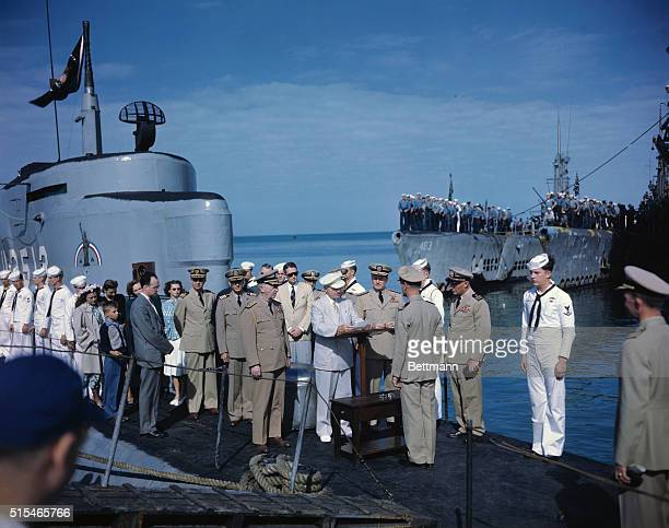 President Truman is shown as he reads a citation for one of the four naval officers he decorated aboard the captured German U-boat, the Ex-U-2513 on...