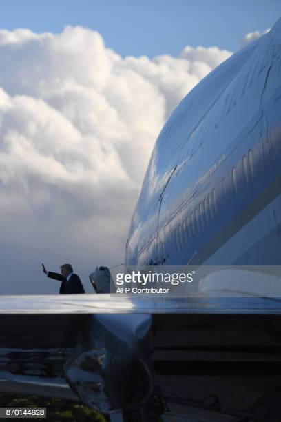 US President Trump waves as he embarks on Air Force One leaving Hawaii for Japan on November 04 2017 After stopping in Hawaii to pay his respects at...