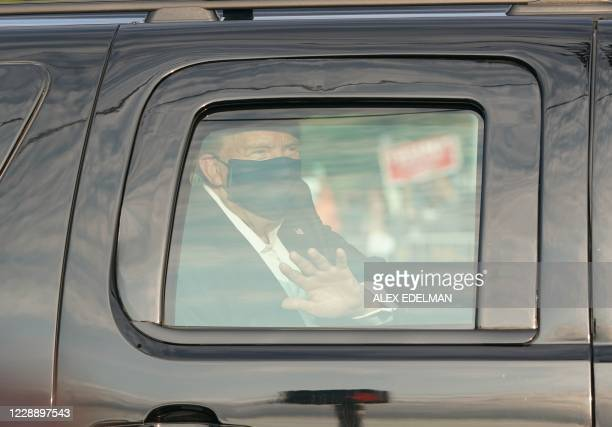 President Trump waves from the back of a car in a motorcade outside of Walter Reed Medical Center in Bethesda, Maryland on October 4, 2020.