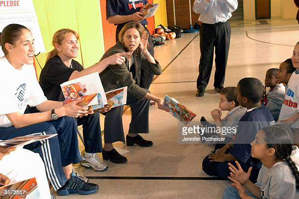 WNBA President Val Ackerman Connecticut Sun member Debbie Black and former WNBA player Rebecca Lobo read to kids at a basketball and books clinic for...