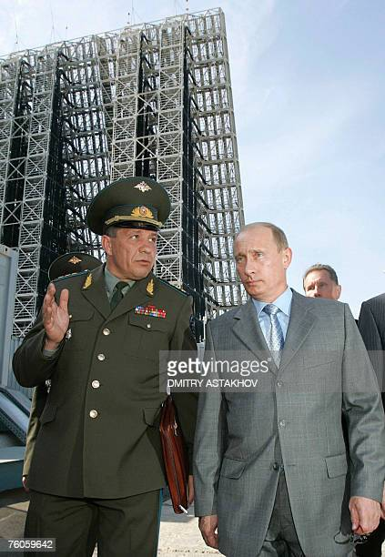 President Vladimir Putin listens to Colonel General Vladimir Popovkin commander-in-chief of the space forces, during his visit to the new-generation...