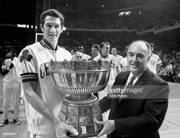 NBA President Walter Kennedy and John Havlicek of the Boston Celtics pose with the Walter Brown Memorial trophy circa 1969 at the Boston Garden in...