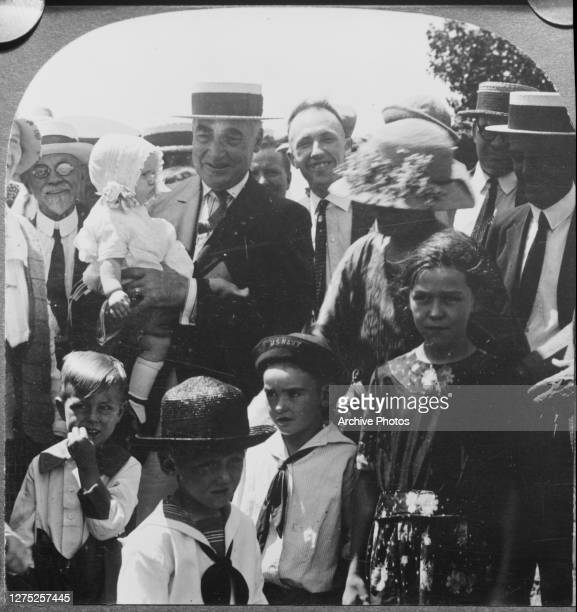 President Warren G Harding holding a baby whilst visiting farmers in Hutchinson, Kansas, 23rd June 1923. He is on his 'Voyage of Understanding' tour...