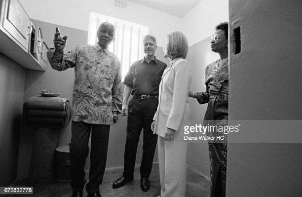 President William Clinton First Lady Hillary Rodham Clinton President Nelson Mandela and Graca Machel are photographed in the jail cell where Mandela...