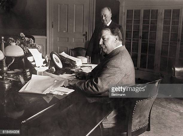 President William Howard Taft at his desk signing the Reciprocity Bill Secretary Philander C Knox is shown standing in the background Undated...