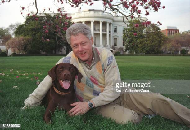 President William Jefferson Clinton posing with Buddy the Dog outside of the White House, April 6, 1999. Image courtesy National Archives. .