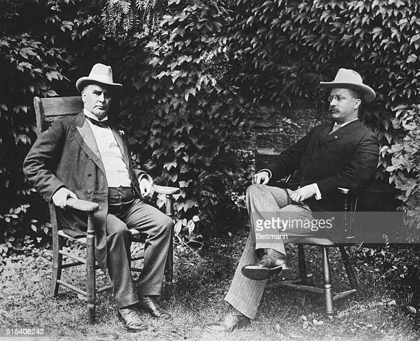President William McKinley , President from 1897-1901, and Vice President Theodore Roosevelt seated outdoors in front of an ivy covered stone wall....