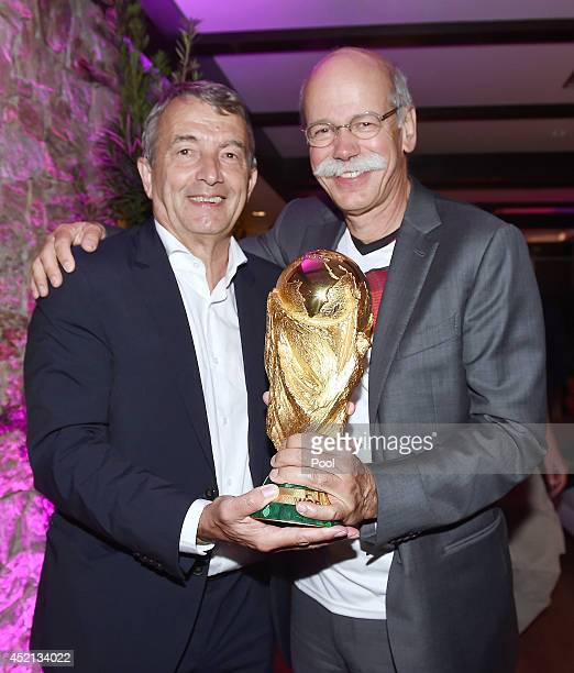DFB president Wolfgang Niersbach and Chairman of Daimler AG Dieter Zetsche pose with the World Cup trophy as they celebrate at a party after winning...