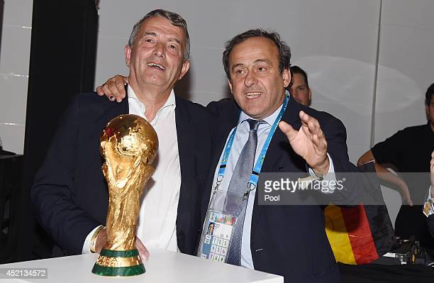 DFB president Wolfgang Niersbach and UEFA President Michel Platini pose with the World Cup trophy as they celebrate at a party after winning the 2014...
