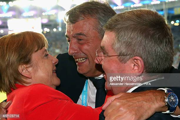 President Wolfgang Niersbach celebrate winning the World Cup with German Chancellor Angela Merkel and IOC President Thomas Bach after the 2014 FIFA...