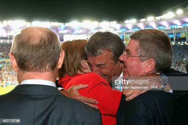 President Wolfgang Niersbach celebrate winning the World Cup with German Chancellor Angela Merkel Russian President Vladimir Putin and IOC President...