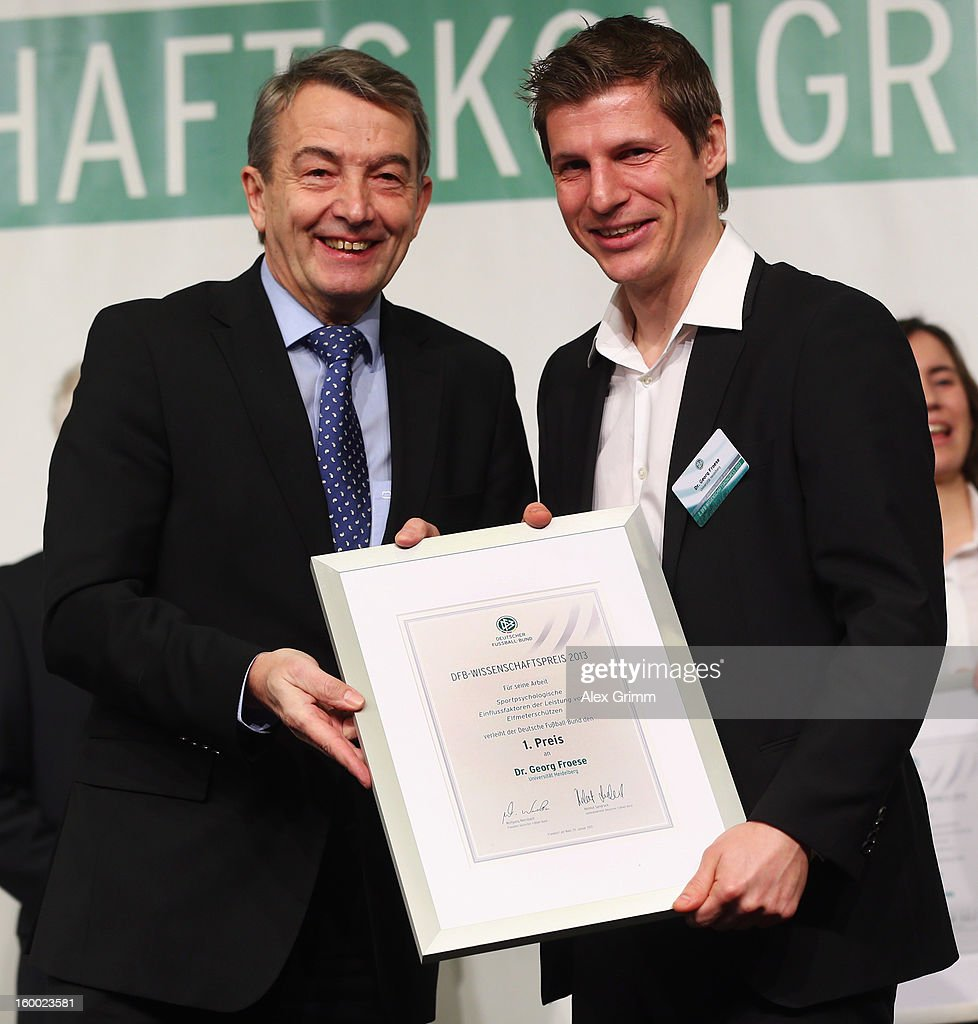 DFB president Wolfgang Niersbach hands over the certificate to DFB Science Award winner Georg Froese during the DFB Science Congress 2013 at the Steigenberger Airport Hotel on January 25, 2013 in Frankfurt am Main, Germany.