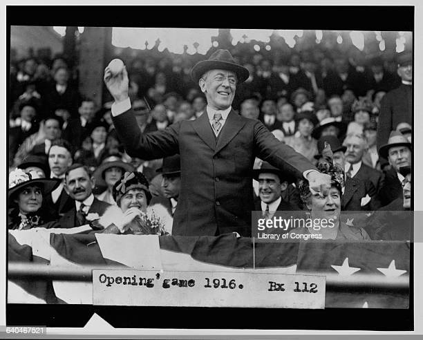 President Woodrow Wilson throws out the first pitch at a seasonopening baseball game in 1916 Mrs Wilson behind him laughs as she watches