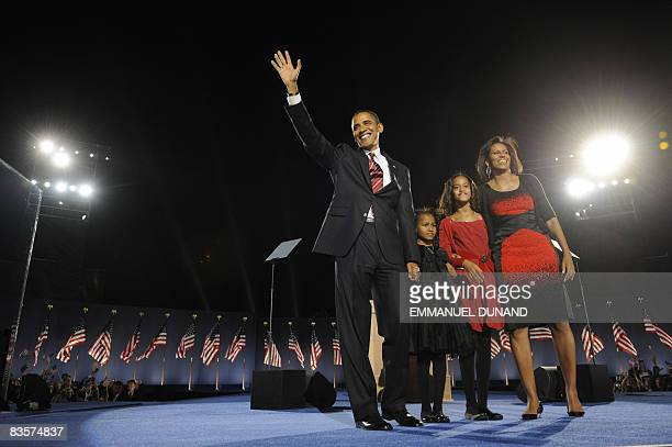 US Presidentelect Barack Obama acknowledges the crowd falnked by his wife Michelle and daughters Sasha and Malia at his election night party in...