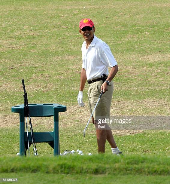 US Presidentelect Barack Obama acknowledges the media as he warms up on the driving range to play golf with friends December 29 2008 in Kailua Hawaii...