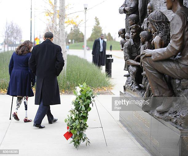 US Presidentelect Barack Obama escorts Gulf War veteran Tammy Duckworth after honoring America's veterans on Veterans Day at the Bronze Soldiers...