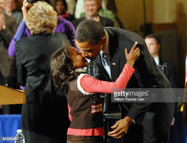 S Presidentelect Barack Obama kisses his daughter Sasha at a gathering of supporters before the Obamas embark on a whistlestop train trip to...