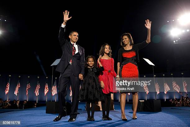Presidentelect Barack Obama left his wife Michelle Obama right and two daughters Malia and Sasha center left wave to the crowd at the election night...