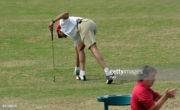US Presidentelect Barack Obama replaces a divot as he warms up on the driving range to play golf with friends December 29 2008 in Kailua Hawaii Obama...