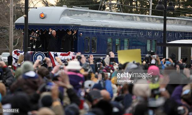 Presidentelect Barack Obama right and Vice Presidentelect Joseph Biden wave as their train passes through Edgewood Maryland US during the Whistle...