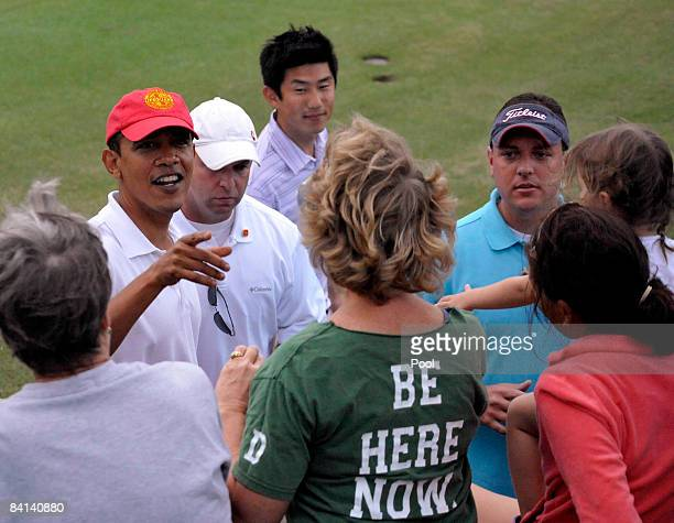 President-elect Barack Obama smiles as he shakes hands with well wishers in a crowd gathered beside the 18th hole after finishing a round of golf...