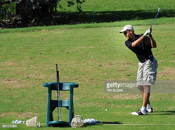 US Presidentelect Barack Obama warms up on the driving range before a Christmas eve round of golf with friends on December 24 2008 at the Mid Pacific...