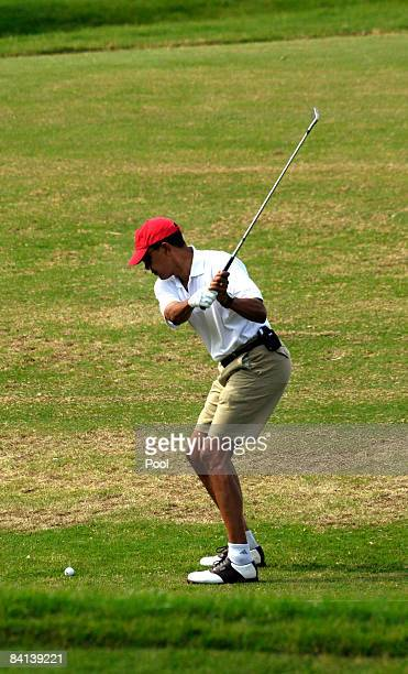 US Presidentelect Barack Obama warms up on the driving range to play golf with friends December 29 2008 in Kailua Hawaii Obama and his family have...
