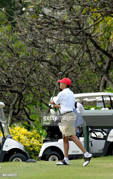 US Presidentelect Barack Obama watches his tee shot off on the tenth hole as he plays golf with friends December 29 2008 in Kailua Hawaii Obama and...