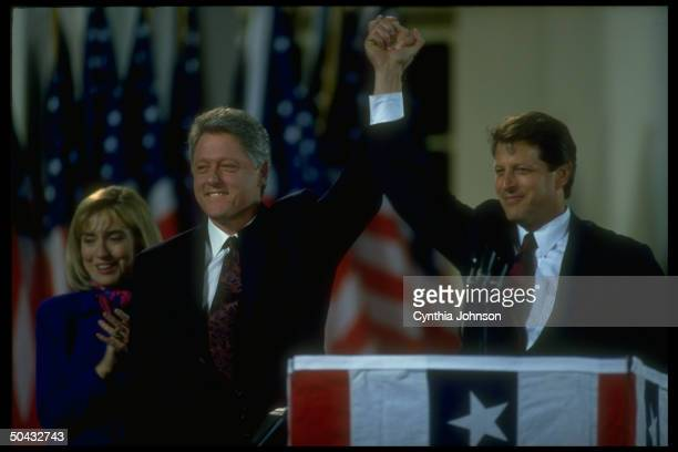 Presidentelect Bill Clinton VPelect Al Gore raising hands in triumph with Hillary Rodham Clinton looking on at election night celebratory rally