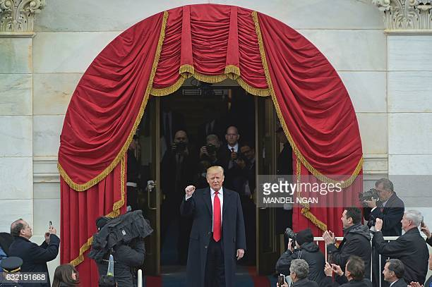 TOPSHOT Presidentelect Donald Trump acknowledges guests as he arrives on the platform at the US Capitol in Washington DC on January 20 during his...