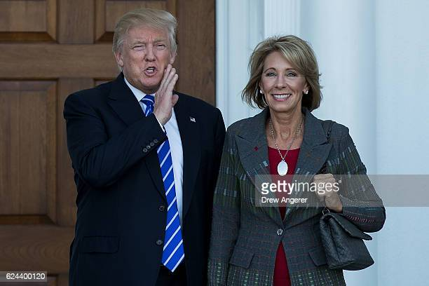 presidentelect Donald Trump and Betsy DeVos pose for a photo after their meeting at Trump International Golf Club November 19 2016 in Bedminster...