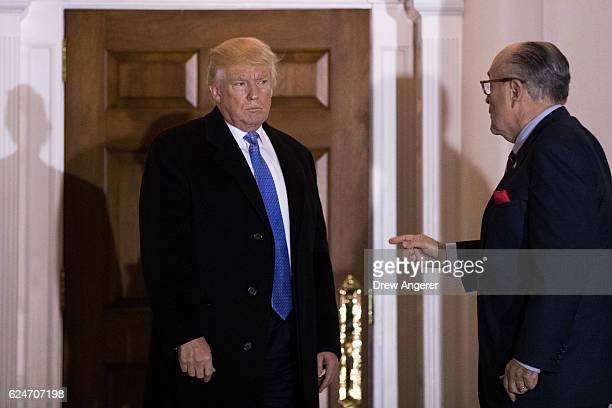 Presidentelect Donald Trump and former New York City mayor Rudy Giuliani talk to each other as they exit the clubhouse following their meeting at...