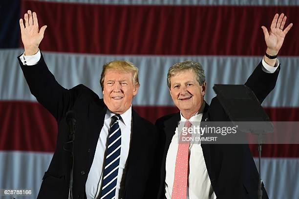 US Presidentelect Donald Trump and Louisiana Treasurer and Republican Senate candidate John Kennedy wave at a getoutthevote rally on December 9 2016...