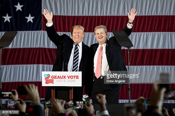 Presidentelect Donald Trump and Republican US Senate candidate from Louisiana John Kennedy wave to the crowd at a rally at the Dow Chemical Hangar...