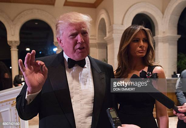 US Presidentelect Donald Trump answers questions from reporters accompanied by his wife Melania for a New Year's Eve party December 31 2016 at...