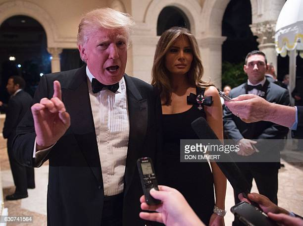 Presidentelect Donald Trump answers questions from reporters accompanied by wife Melania for a New Year's Eve party December 31 2016 at MaraLago in...