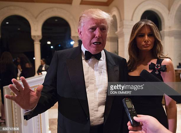 US Presidentelect Donald Trump answers questions from reporters accompanied by wife Melania for a New Year's Eve party December 31 2016 at MaraLago...