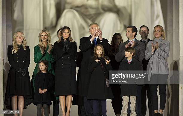 US Presidentelect Donald Trump applauds while standing with his family during the 'Make America Great Again' Welcome Celebration concert at the...