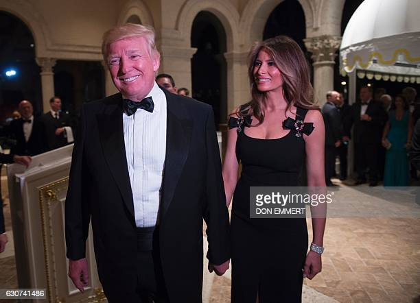 US Presidentelect Donald Trump arrives with his wife Melania for a New Year's Eve party December 31 2016 at MaraLago in Palm Beach Florida / AFP /...