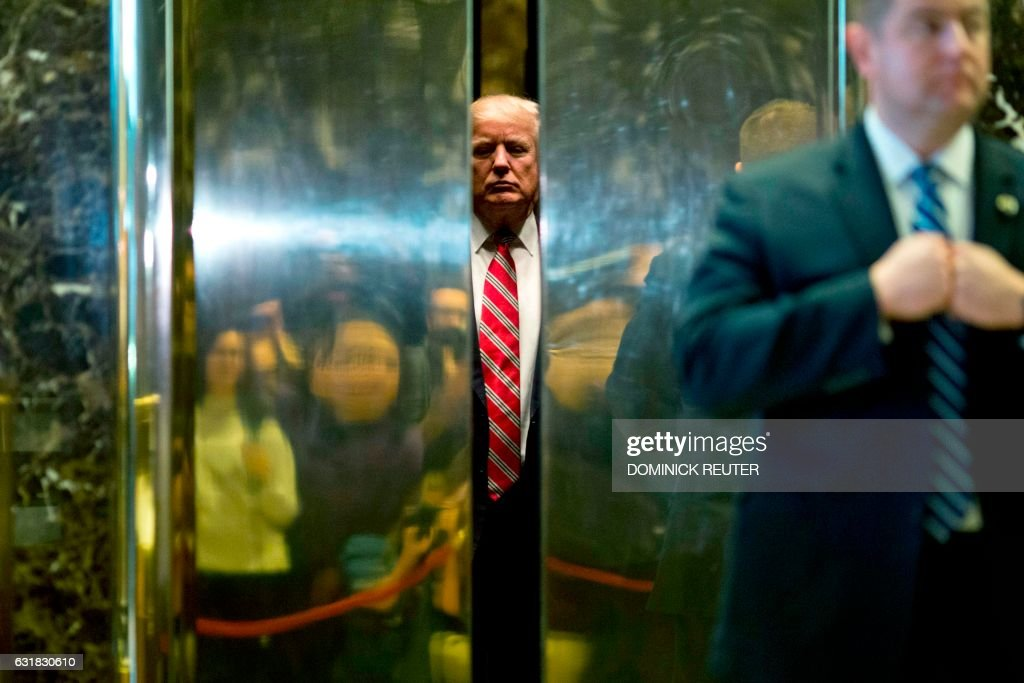 US President-elect Donald Trump boards the elevator after escorting Martin Luther King III to the lobby after meetings at Trump Tower in New York City on January 16, 2017. /
