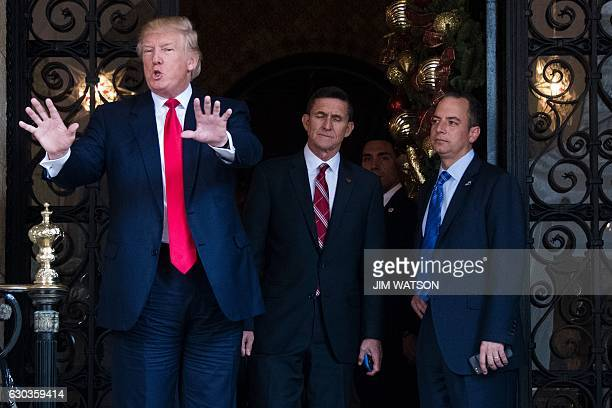 US Presidentelect Donald Trump gestures as he speaks with Trump National Security Adviser Lt General Michael Flynn and Trump Chief of Staff Reince...